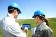 Engineers using tablet on wind turbine site