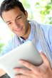 Handsome guy websurfing on internet with tablet