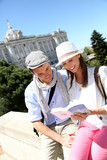 Couple reading traveler book by the Royal Palace of Madrid