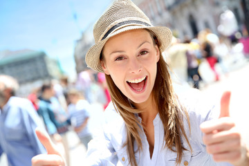 Portrait of cheerful girl in town showing thumbs up