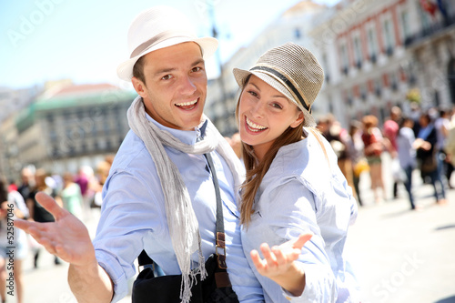 Cheerful couple in Madrid showing thumbs up