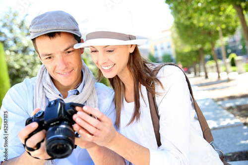 Cheerful couple with photo camera in touristic area