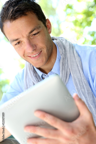 Handsome guy websurfing on internet with tablet