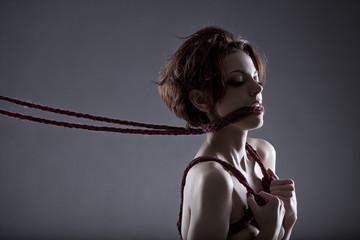 Passionate red-haired model tied with rope