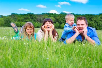 junge familie lachend auf der wiese