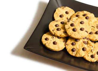 Chocolate chip cookies on a black plate isolated on white backgr