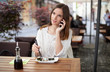 Beautiful young woman talking on the phone in a sushi restaurant