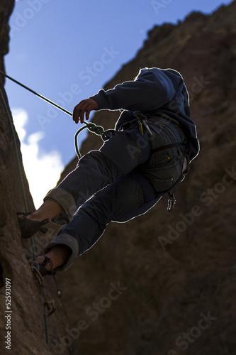 Escalador rapelando a cotralluz. Piedra, montaña, deporte.