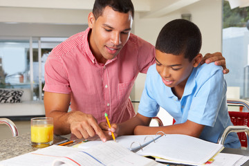 Father Helping Son With Homework In Kitchen