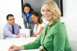 Portrait Of Businesswoman In Boardroom With Colleagues