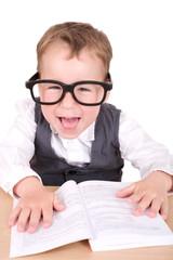 Kleiner Junge lacht in die Kamera mit Brille und Buch