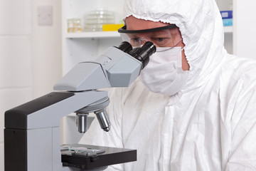 Lab technician looking through a microscope