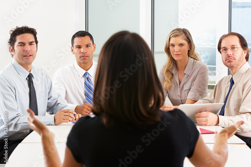 View From Behind As CEO Addresses Meeting In Boardroom