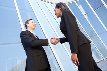 Businessman And Businesswomen Shaking Hands Outside Office