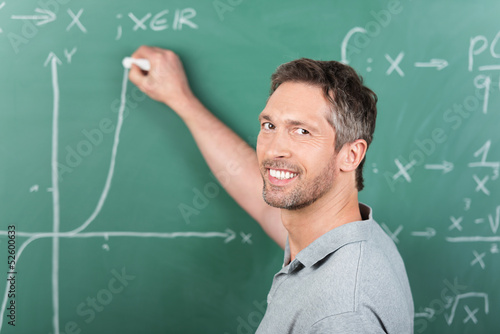 lehrer schreibt matheaufgabe an die tafel