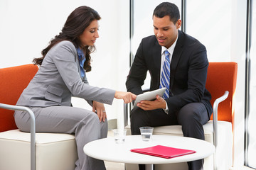 Businessman And Businesswoman Having Informal Office Meeting