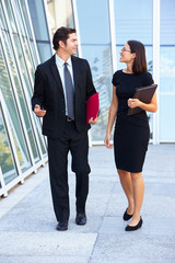 Businessman And Businesswomen Walking Outside Office
