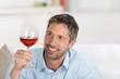 lächelnder mann schaut auf ein glas rotwein