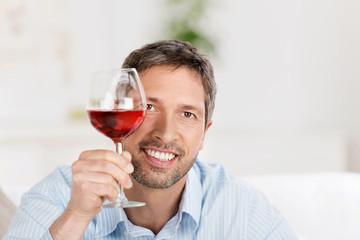lächelnder mann mit einem glas rotwein