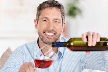 mann schenkt ein glas rotwein ein