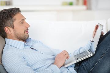 mann liegt mit laptop auf dem sofa