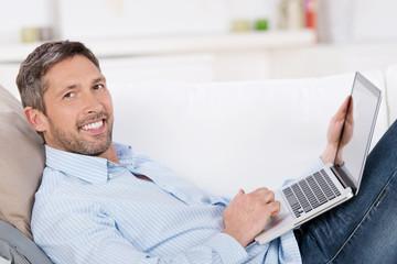 lächelnder mann liegt mit laptop auf dem sofa