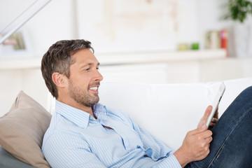 mann mit tablet auf dem sofa