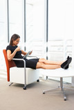 Businesswoman Relaxing With Digital Tablet During Break