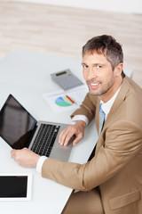geschäftsmann mit laptop und tablet schaut nach oben