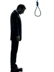 man sad standing in front of  hangman noose silhouette