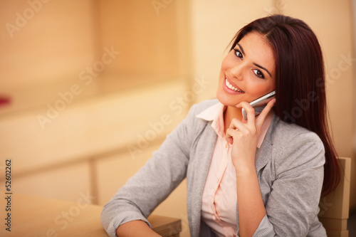business woman talking on cell phone and looking at camera