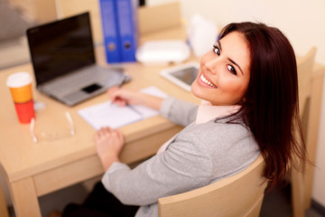 Young businesswoman sitting at desk and working