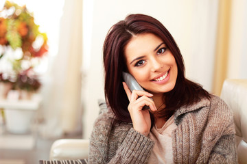 Young happy woman at home talking on phone