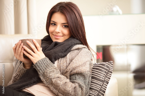 Happy young woman sitting on sofa in cosy cloths