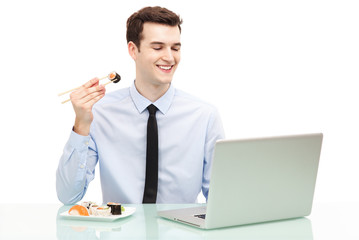 Man with laptop eating sushi