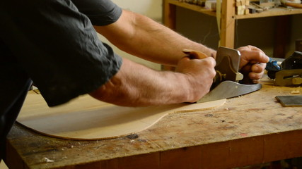 Luthier working with a wood planer in a flamenco guitar