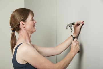 Woman using a hammer to bang a nail