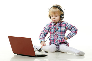 Small child in headset with laptop.