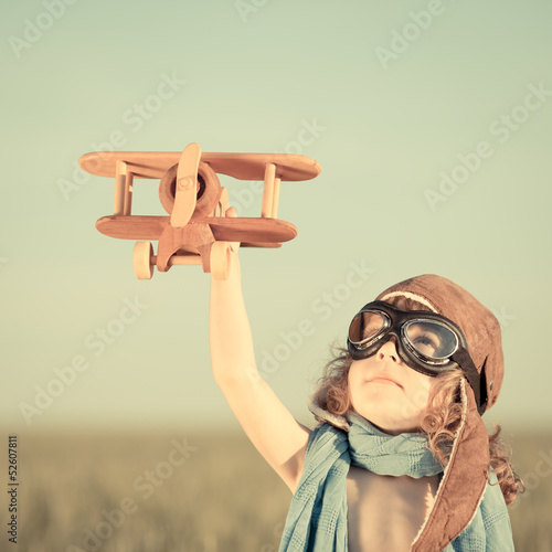 Poster Happy kid playing with toy airplane