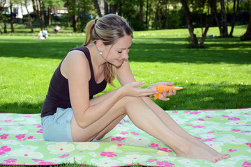 Junge Frau cremt sich mit Sonnenmilch ein