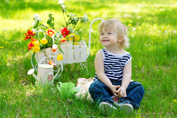 Positive kid sitting on the fresh green grass in the garden