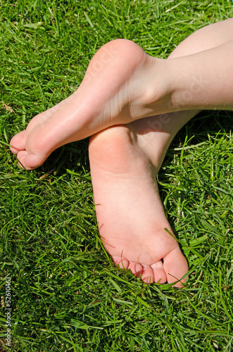 Childs bare feet in green grass