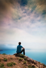 A lonely young man sits on a hill
