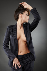 Sexy businesswoman posing on gray background