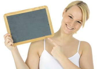Junge Frau zeigt auf leere Tafel