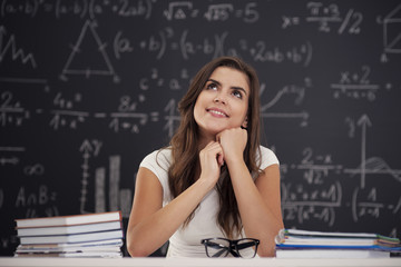 Happy woman sitting in classroom and looking up