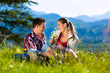 Paar sitzt in auf Wiese vor Bergpanorama