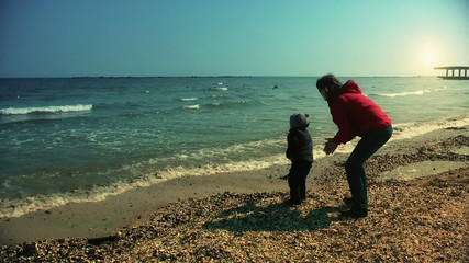 Mother and son playing on the sea shore, slow motion