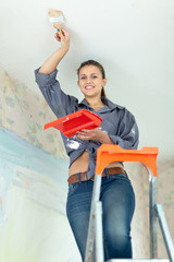 Woman paints ceiling with brush
