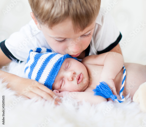 kid boy looking at sleeping newborn baby brother